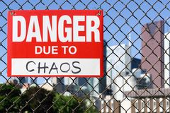 Sign danger due to chaos hanging on the fence. Sign danger due to chaos attached on the fence in the front of the town royalty free stock photography