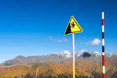 Sign - danger of falling down, Sochi. Yellow warning sign about the danger of falling down the slope. Autumn mountain landscape, views of hills and peaks of Stock Photography