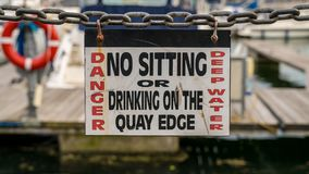 Sign: Danger no sitting or drinking on the quay edge Royalty Free Stock Photo