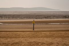 Sign: Danger Sinking Mud. Seen on the beach of Weston-super-Mare, North Somerset, England, UK stock image