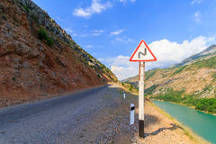 Sign a dangerous curve on a mountain road, near the cliff. Uzbekistan, western Tien-Shan. Summer time royalty free stock photos