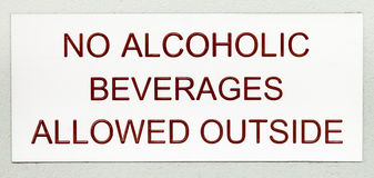 Sign with Dark Red Lettering NO ALCOHOLIC BEVERAGES ALLOWED OUTS Royalty Free Stock Image