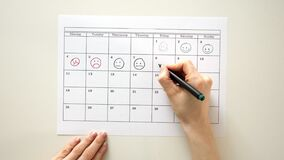 Sign the day in the calendar with a pen, draw a smile. 4k stock footage