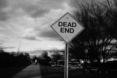 Sign dead end. With a man going away behind it b&w stock photos