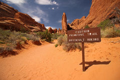 A sign in the desert warns hikers of difficult trail conditions ahead. A sign in the desert reads: `Caution primitive trail, difficult hiking Stock Image