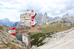 Sign for direction. Alpine hiking trails hint along a trail, on background high rocky mountains, Italy Stock Images