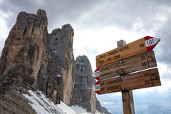 Sign for direction. Alpine hiking trails hint along a trail, on background high rocky mountains, Italy Royalty Free Stock Image