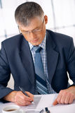 Sign The Document. Elder business manager working on some document in the office Royalty Free Stock Photography