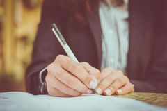 Sign in documents. Close up. Woman writing document. Focus is on hands royalty free stock photography