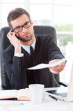 Sign these documents!. Confident young man in formalwear stretching out documents and looking at camera while sitting at his working place Royalty Free Stock Photo