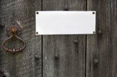 Sign on door. Blank sign pinned to an old wooden door with copy space Royalty Free Stock Photography
