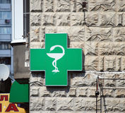 The sign Drugstore at the corner of the house. Green cross Royalty Free Stock Image