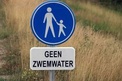 Sign with dutch text `geen zwemwater ` which means in english `no swimming water ` with above sign indicating pedestrian lane;. Sign with dutch text `geen stock photography