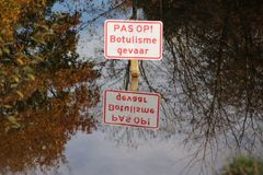 Sign with dutch text Pas op Botulisme gevaar which means Caution, danger for botulism. In the water with surface reflection in public park Schakenbos in stock image