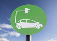 Sign for Electric Car Charging Point. Green sign indicating a charging point for electric vehicles, sunny blue sky added in post-production Royalty Free Stock Photo