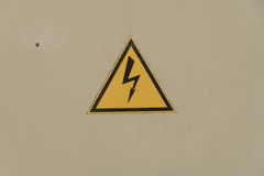 Sign electrical hazard placed on a rusty metal panel. Sign electrical hazard placed on the rusty metal panel stock photo