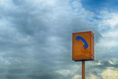 Sign of emergency phone and blue sky background.  royalty free stock photography