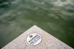 Sign of End of Step Warning by Water. A white circular sign saying in black text: WARNING, End of Step, DO NOTE ENTER THE WATER, with green water in background stock photos