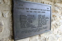 Sign etched with names of famous people passing through the courtyards,Fort Ticonderoga,New York,2014. Big metal plaque on old stone wall, etched with many names royalty free stock image