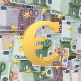 The sign of the euro against cuts. Golden Euro symbol on a background of notes with the stars Stock Images