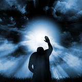 Sign of faith. Silhouette of a person kneeling before a sun Royalty Free Stock Image
