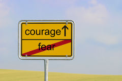 Sign fear courage. Yellow town sign with text fear courage royalty free stock images