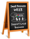 Sign, Folding Easel, Small Business Week. Small Business Week sidewalk chalk board sign, wood frame folding easel with brass chain, slate background with text to Stock Photo