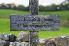 Sign: `For footpath please follow waymarkers`. Seen in the Yorkshire Dales near Bainbridge, North Yorkshire, UK royalty free stock images
