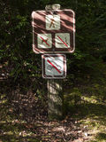 Sign forbidding dogs, smoking and biking on trail Stock Image