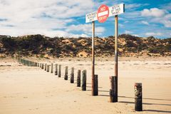 A sign forbidding entry to the beach by unauthorized cars. A sign forbidding entry to the beach by unauthorised cars, standing in the middle of the beach royalty free stock image
