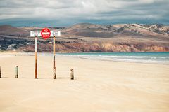 A sign forbidding entry to the beach by unauthorised cars. Standing next to water royalty free stock images