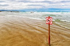 The sign forbidding to bathe on the beach. The sandy beach, the sign on a wooden column is thrust in sand in the leaving wave. Appears through sand, a royalty free stock photography