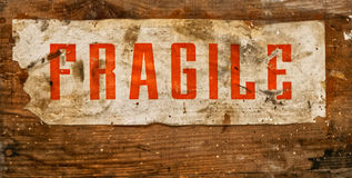 Sign with FRAGILE charming, old and worn, glued on a wooden board Stock Images