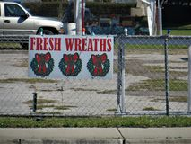 Florida Christmas, Fresh Wreaths. Sign for fresh Christmas wreaths on chain link fence around vacant lot stock images