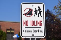No Idling Children Breathing Sign. Sign in front of a brick building stating that vehicles should not idle as there are children breathing nearby. Stick figure royalty free stock photo