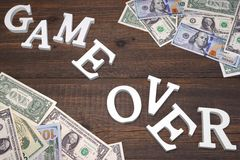 Sign Game Over And Dollars Bills On The Wood Background Stock Image