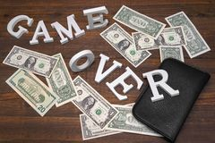 Sign Game Over Dollars And Empty Purse On Wood Background Royalty Free Stock Images