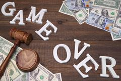 Sign Game Over, Doolars Cash, Judges Gavel On Wood Background Stock Photography