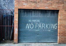 Sign on garage door in laneway near gate saying NO PARKING THIS MEANS YOU. Industrial lane with gate and brick wall with roller garage door with sign NO PARKING royalty free stock photos