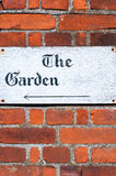 Sign for 'The Garden' on a brick wall background. Sign for 'The Garden' on a brick wall Stock Photography