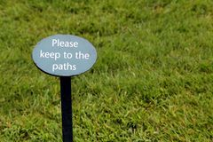 Sign in a grass lawn saying & x22;Please keep to the paths& x22;.  Royalty Free Stock Photo