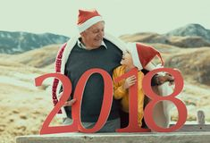 2018 sign in the hands of a senior caucasian man and little boy. 2018 sign in the hands of a senior caucasian men and little boy outdoor. New Year concept Royalty Free Stock Photography