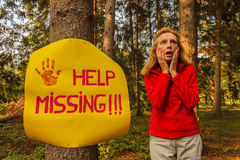 A sign hanging from a tree with the inscription help missing and. A woman after hanging a sign on a tree to ask for help, wandering disoriented in the woods Royalty Free Stock Photo