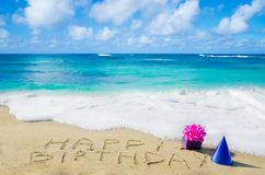 Sign. Happy Birthday with decoration on the sandy beach by the ocean Stock Photos