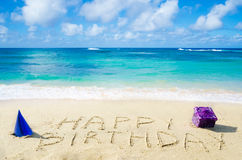 Sign. Happy Birthday with decoration on the sandy beach by the ocean Royalty Free Stock Photos