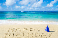 Sign. Happy Birthday with hat on the sandy beach by the ocean Royalty Free Stock Photos