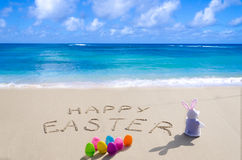 Sign. Happy Easter with bunny and color eggs on the sandy beach by the ocean Royalty Free Stock Photography