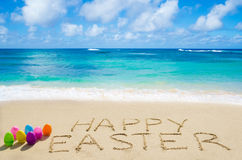 Sign. Happy Easter with color eggs on the on the sandy beach by the ocean Stock Image