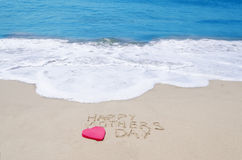 Sign. Happy mothers day on the sandy beach next to ocean Stock Images