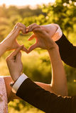 Sign heart. The bride and groom show the hand sign of the heart with an arrow Stock Photo